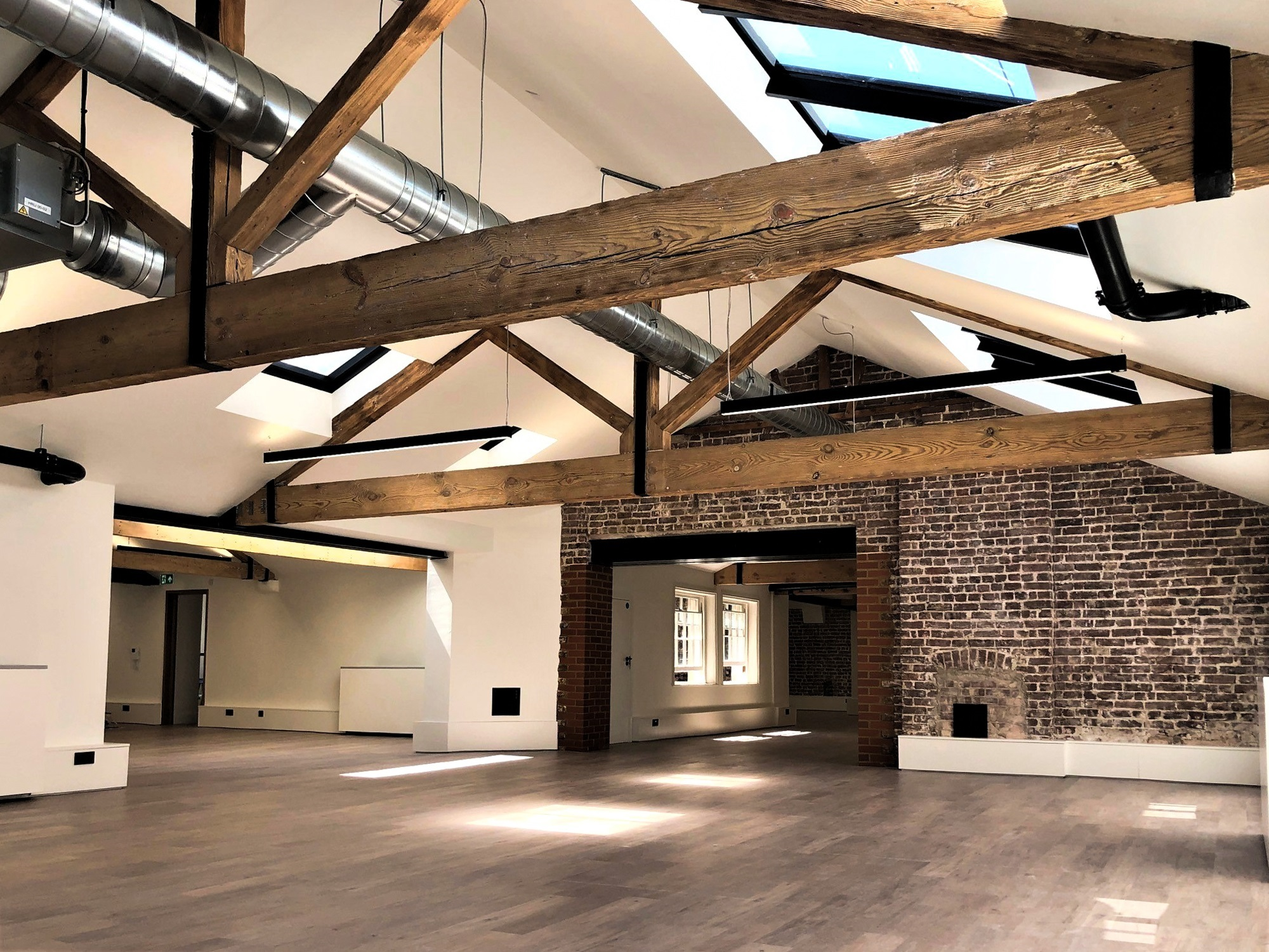 an empty building with exposed wooden beams and a brick wall