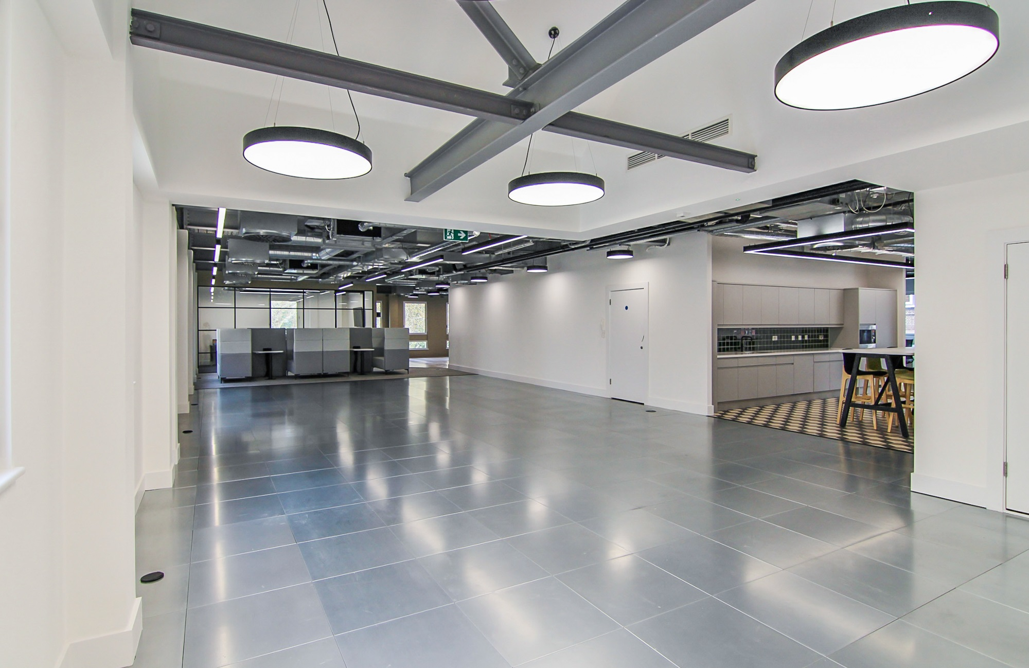 empty office floor with exposed metal and circulars lights