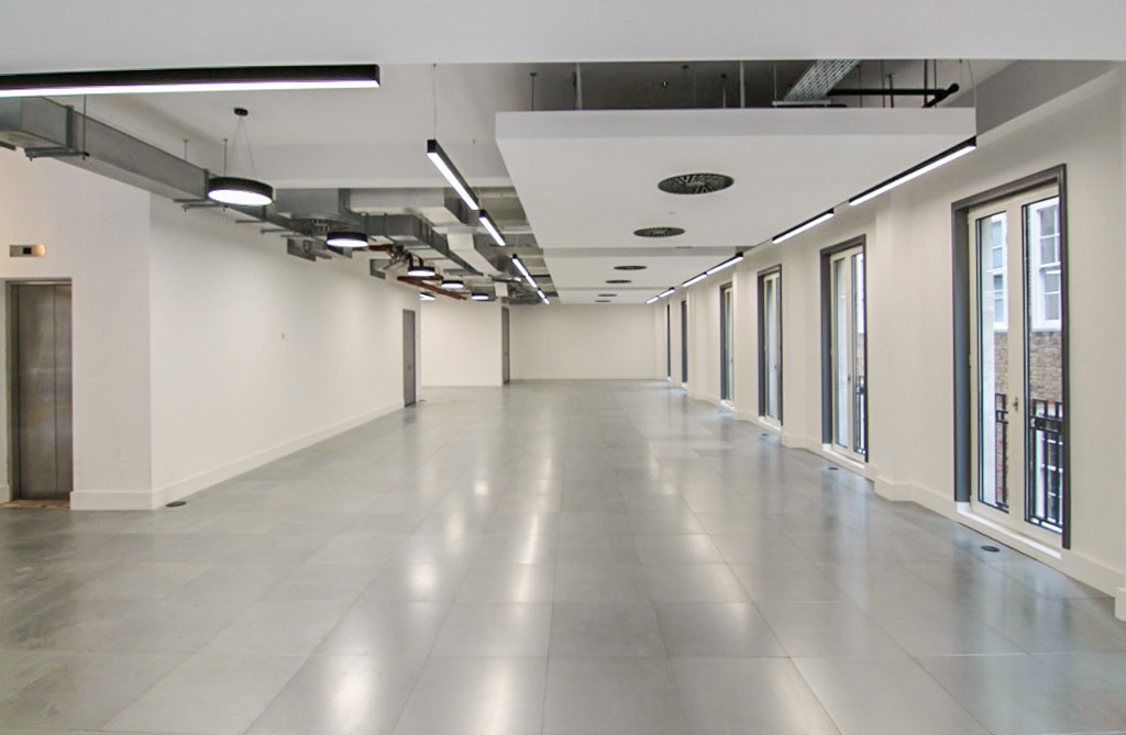 empty office floor with exposed ceiling lightings and vents