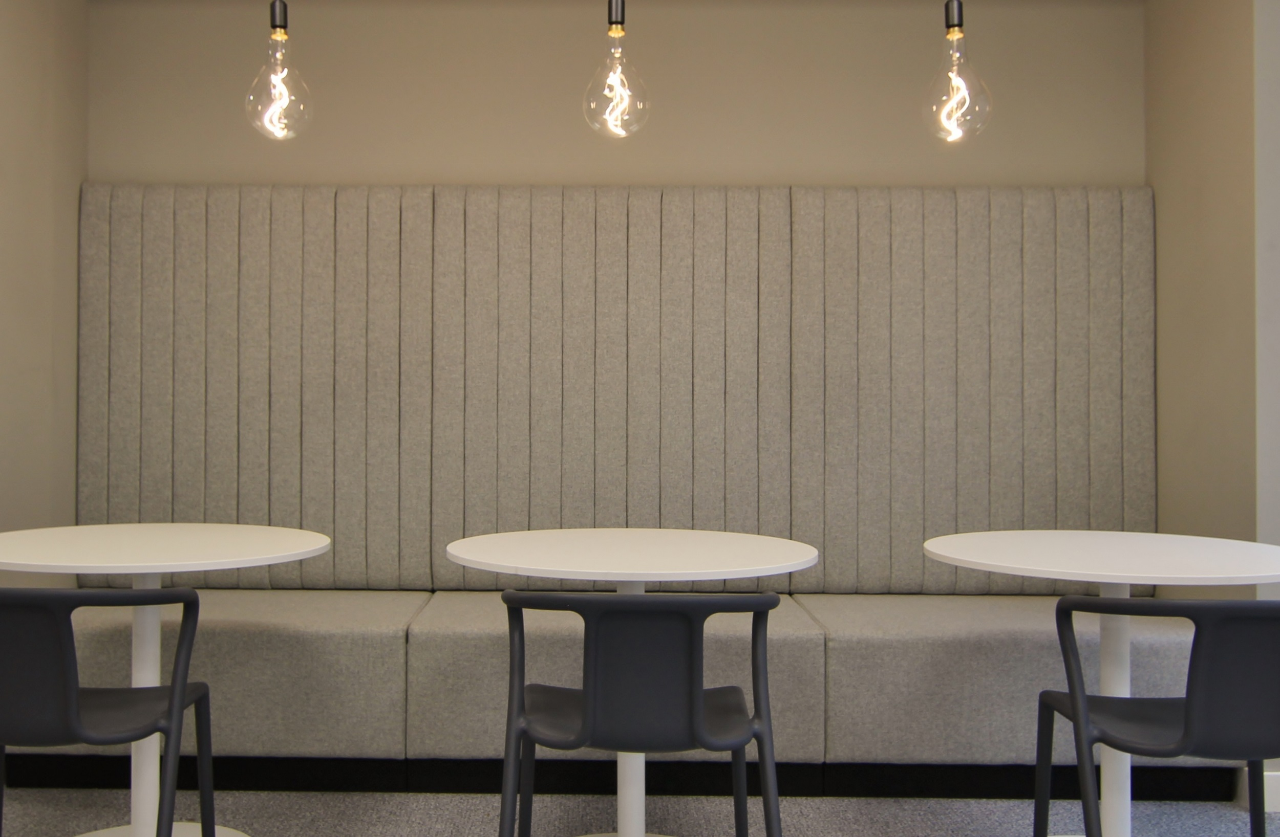 three large light bulbs hanging above three tables and chairs
