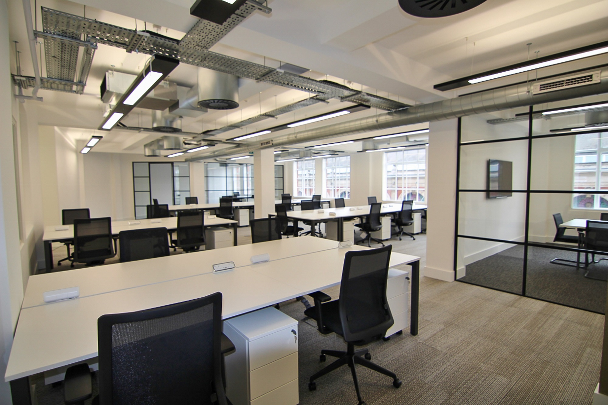 empty office with chairs, desk, and exposed ceiling