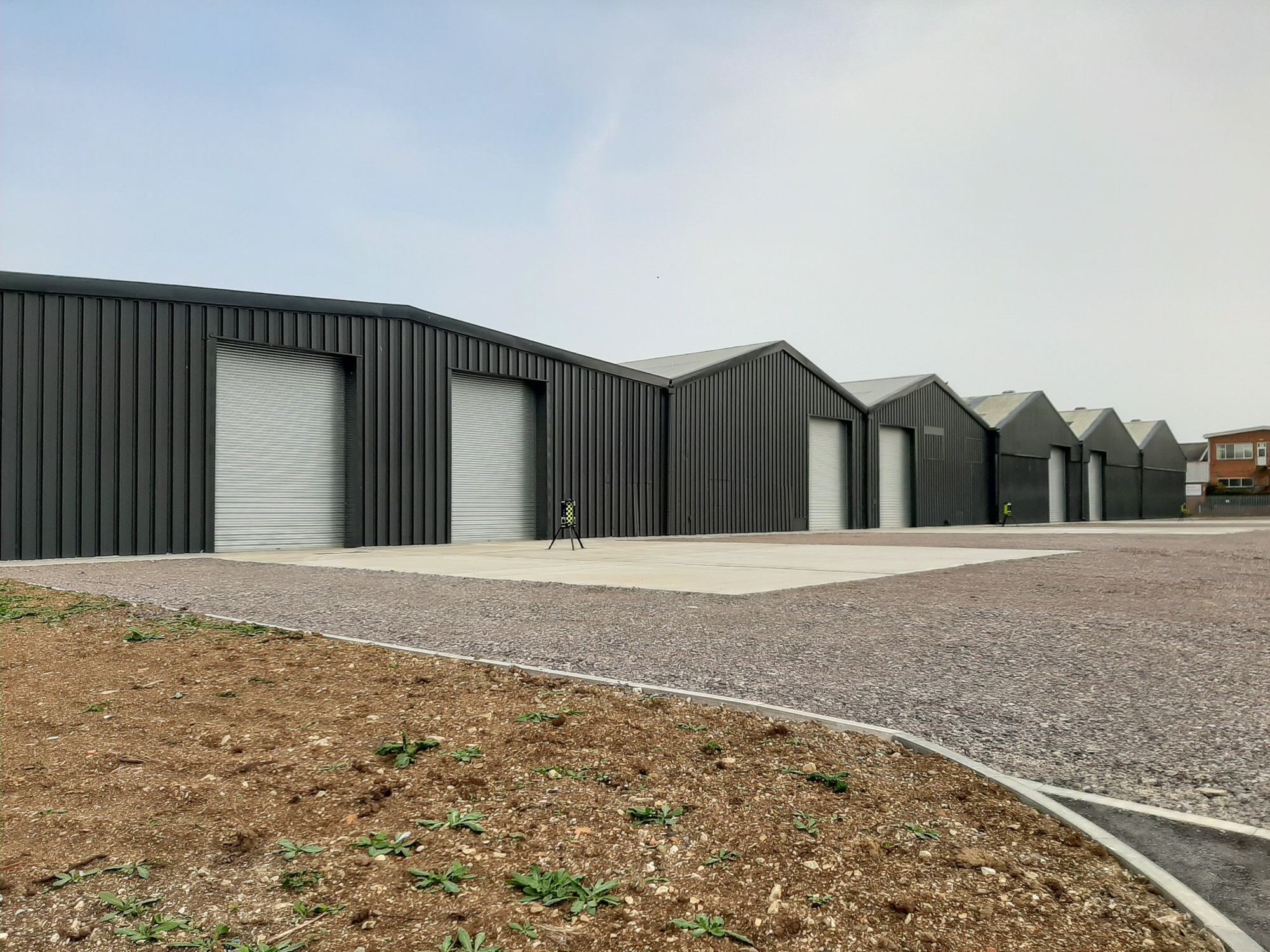 a row of large black warehouses with tarmac ground