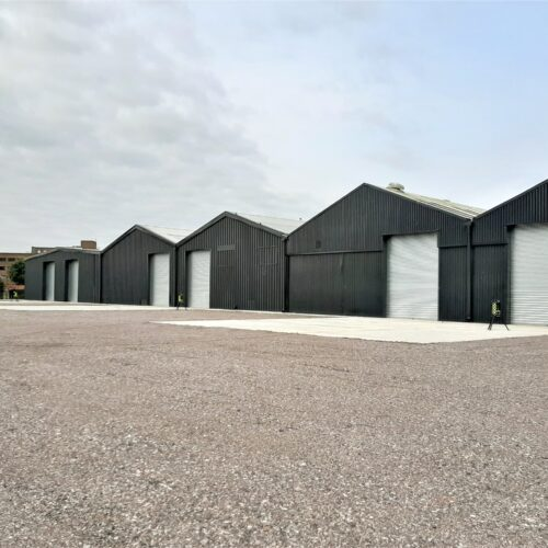 a row of black warehouses with silver doors