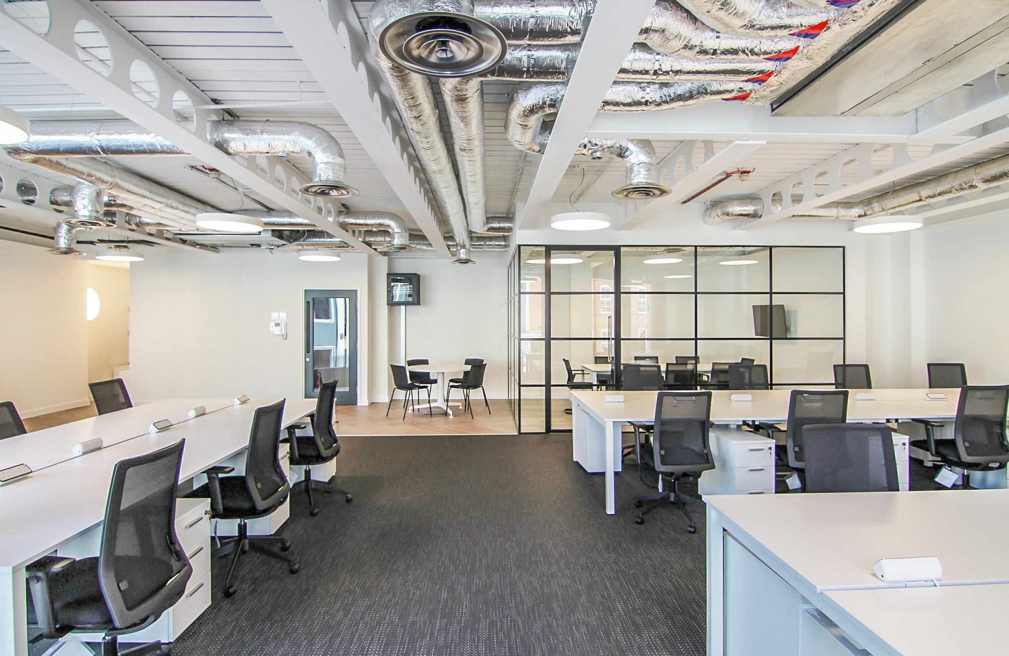 an open office with tables and black chairs