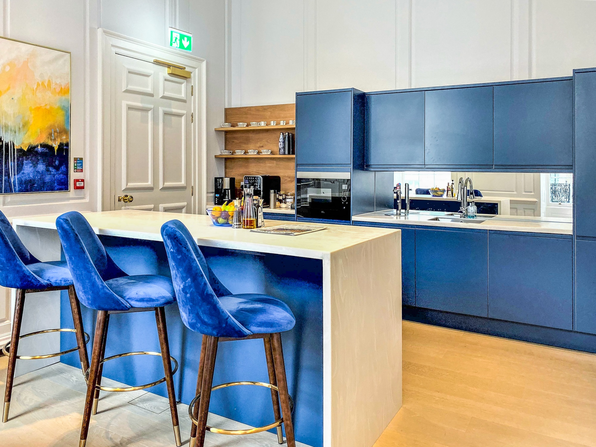 kitchen with blue cupboards and bar stools