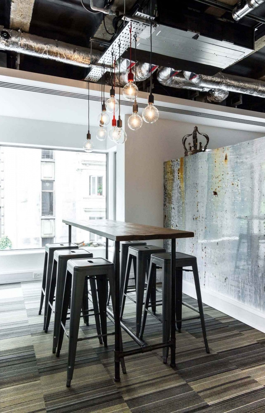 tall metal seating stools under a table