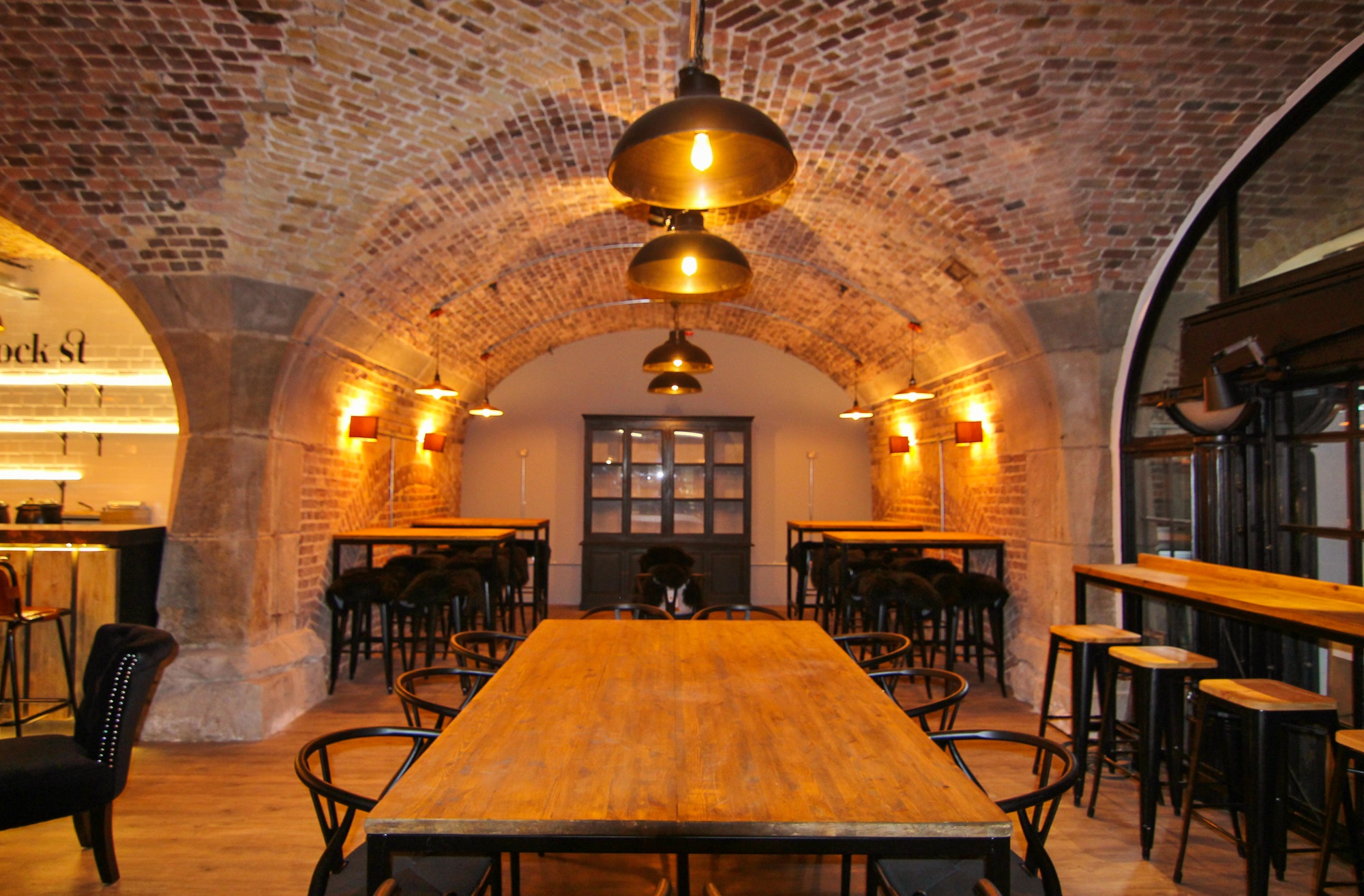 tables and chairs located in a room with an exposed brick ceiling