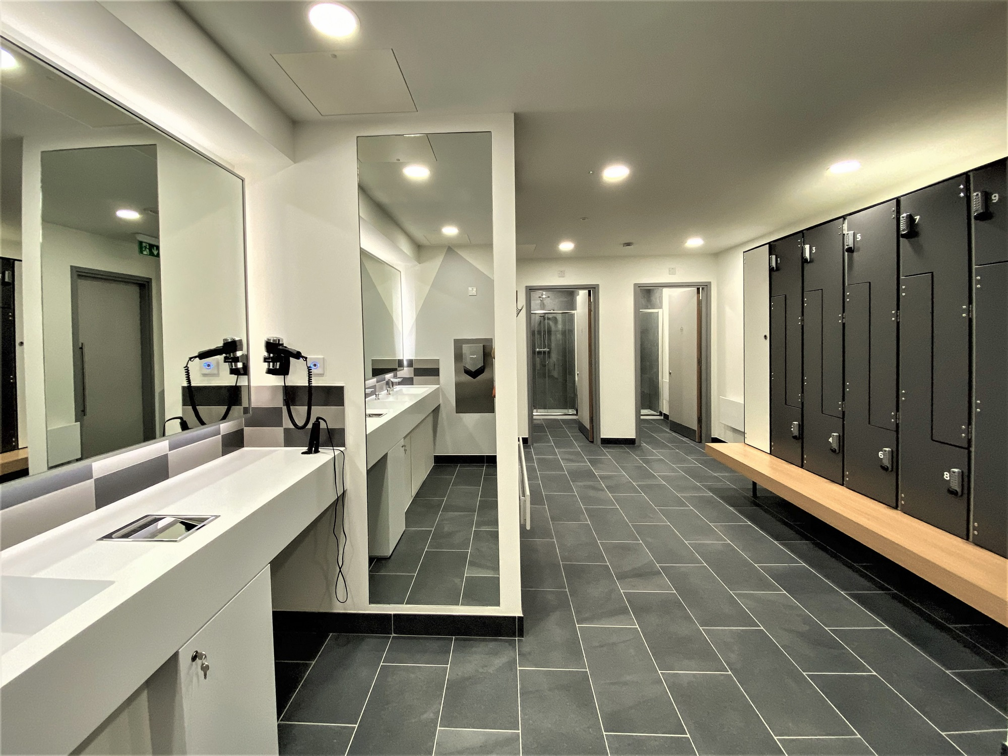 modern changing room with lockers and a full-size mirror