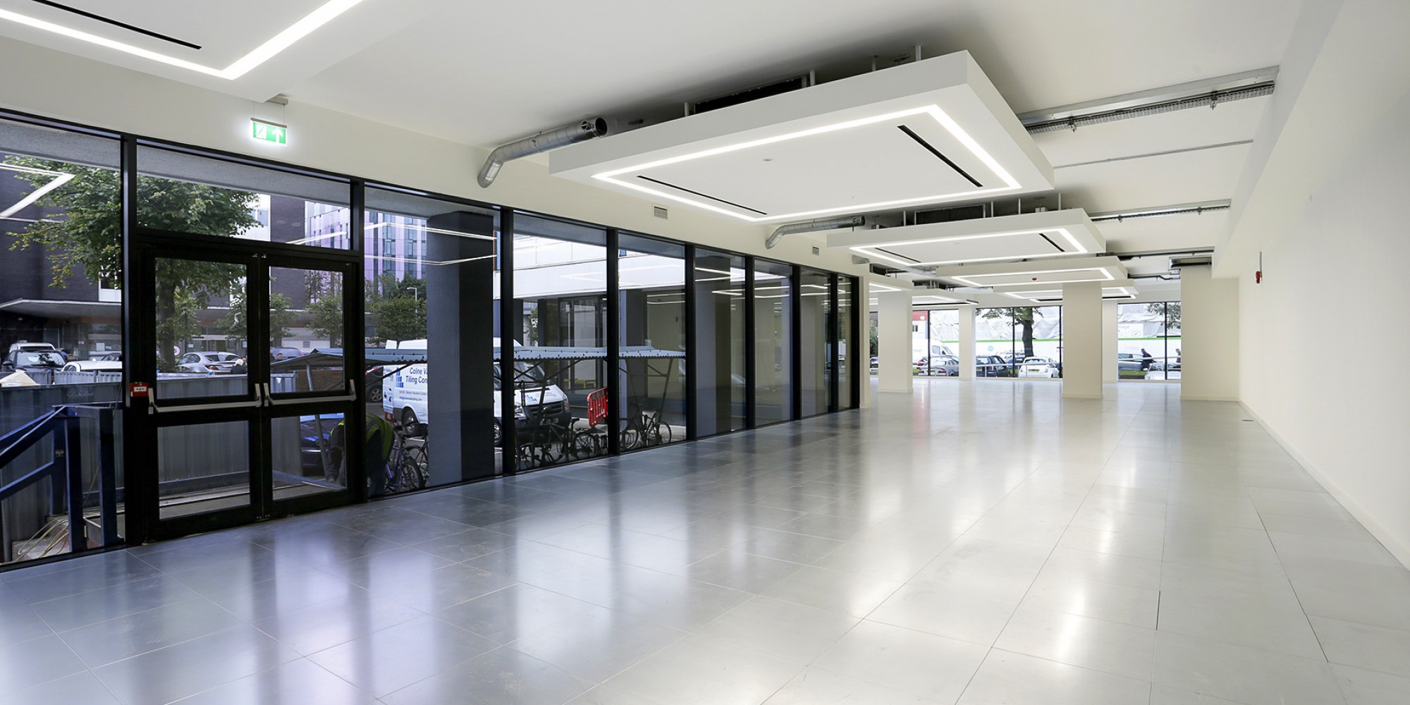 refurbished empty office space with white ceiling and tinted windows