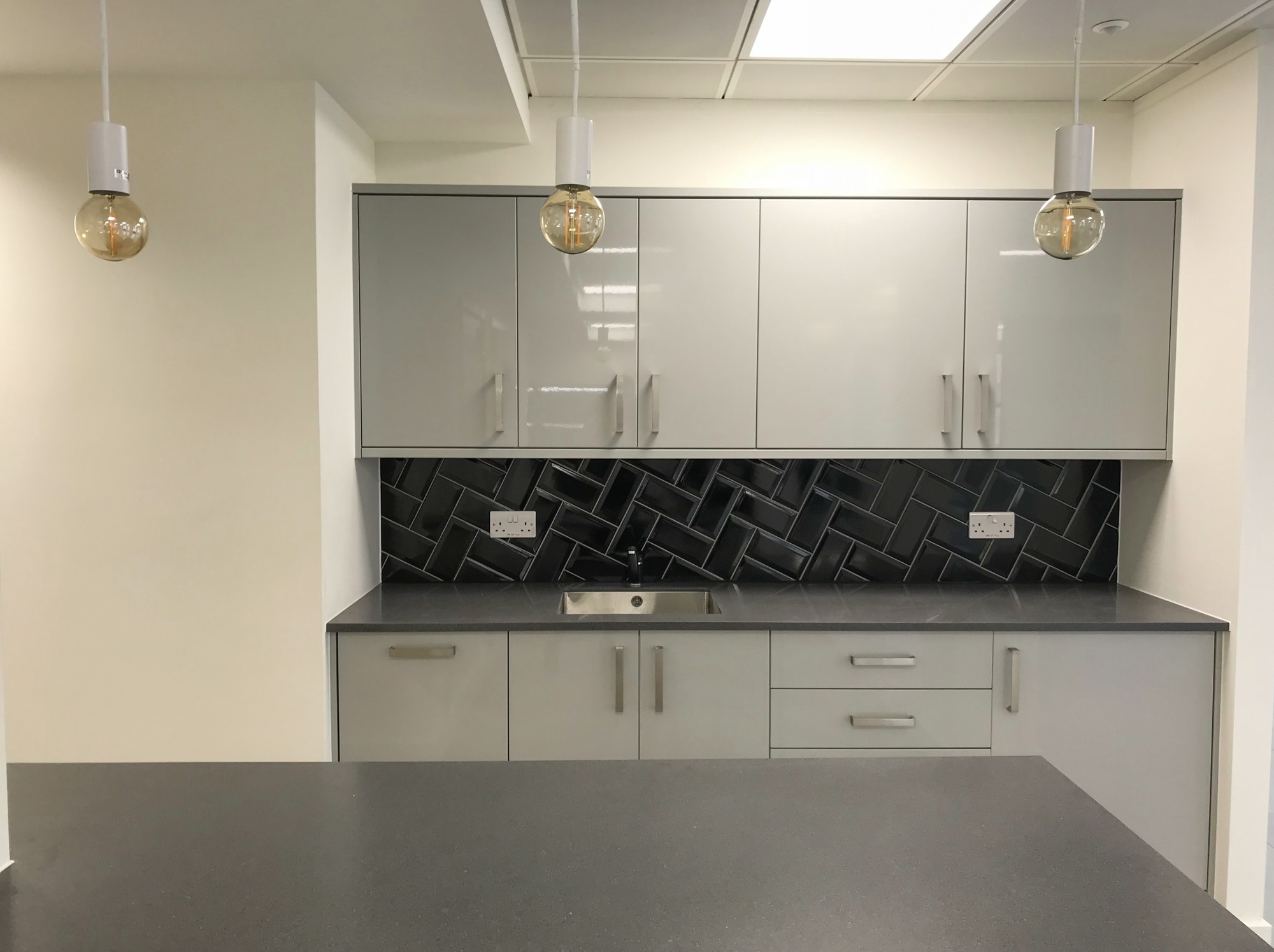 modern kitchen with glossy grey cupboards and worktop