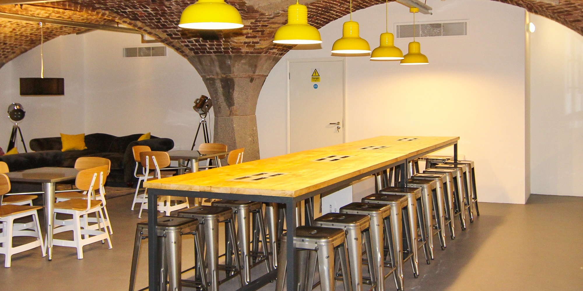 large table with metal stools and yellow dome light shades