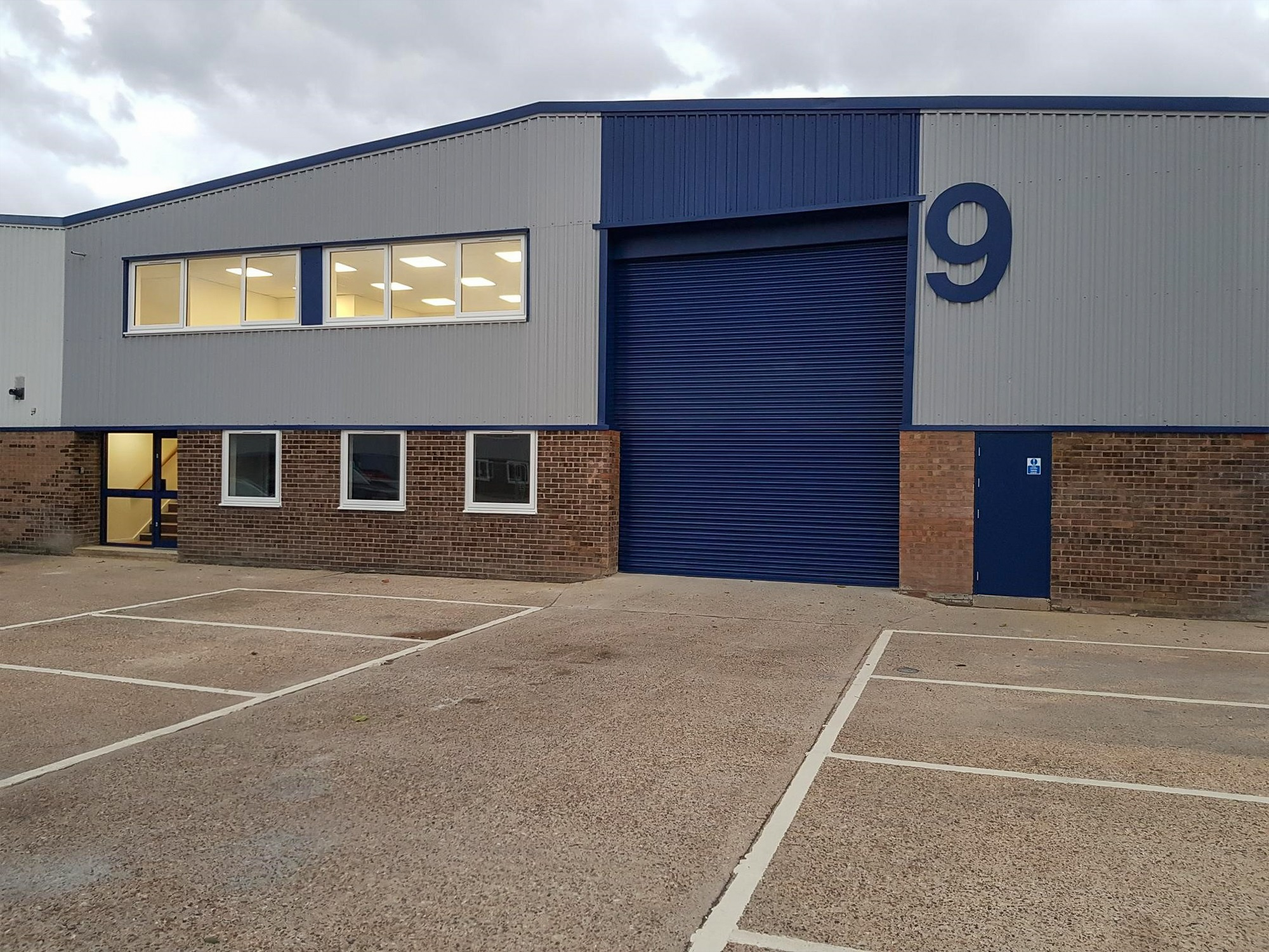 warehouse unit with a large blue door and roof