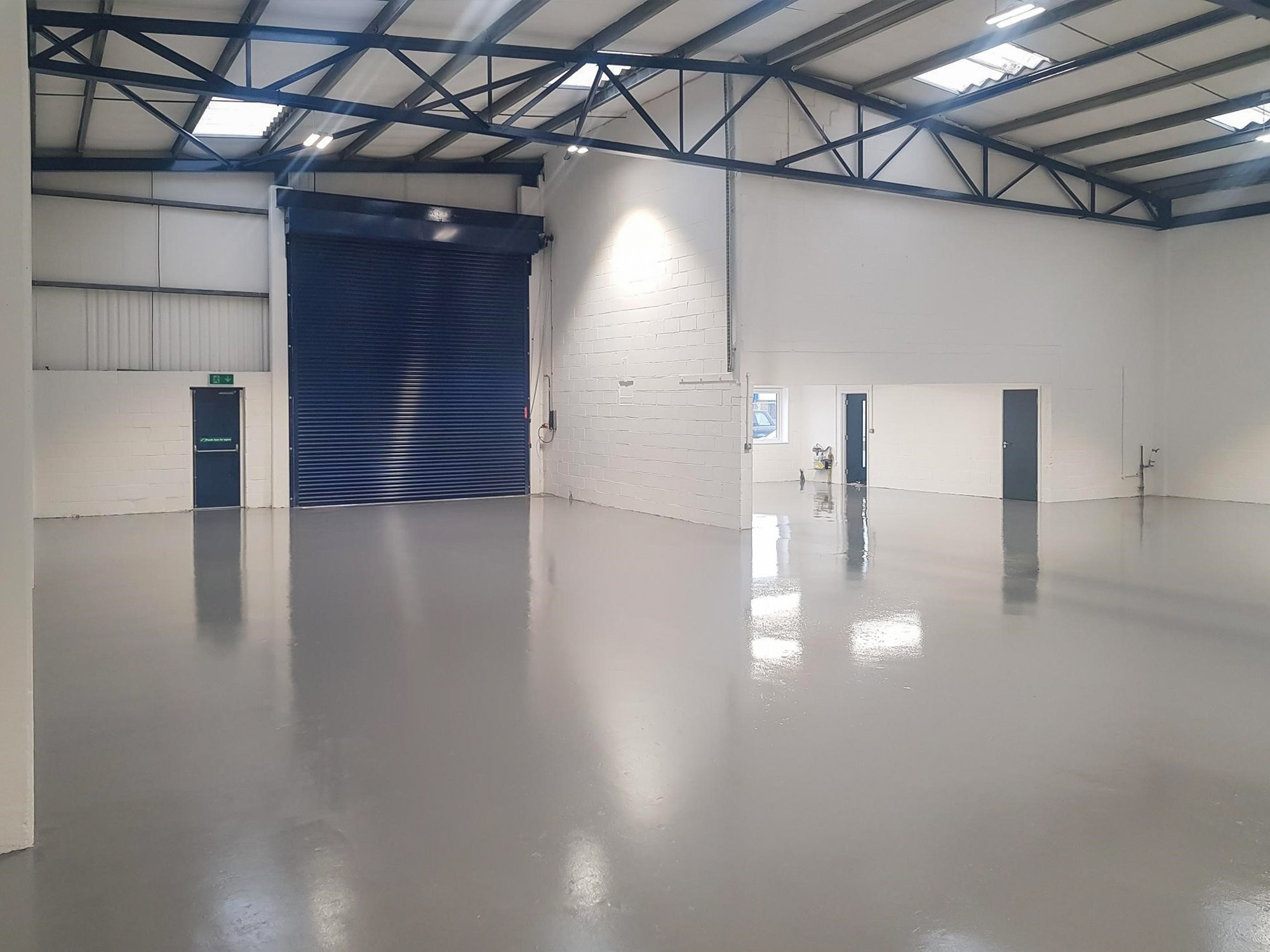 empty warehouse with a white floor, doors and blue walls