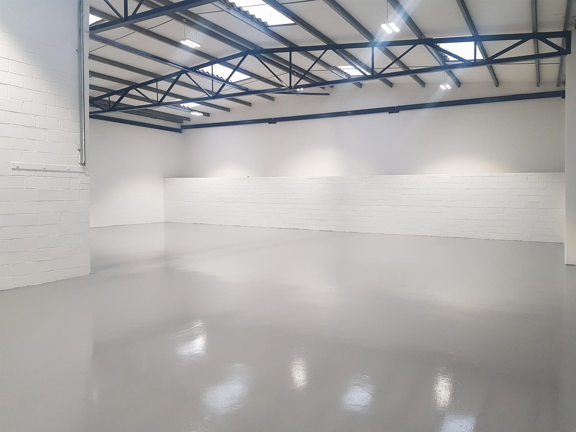 empty warehouse with a white floor and wall