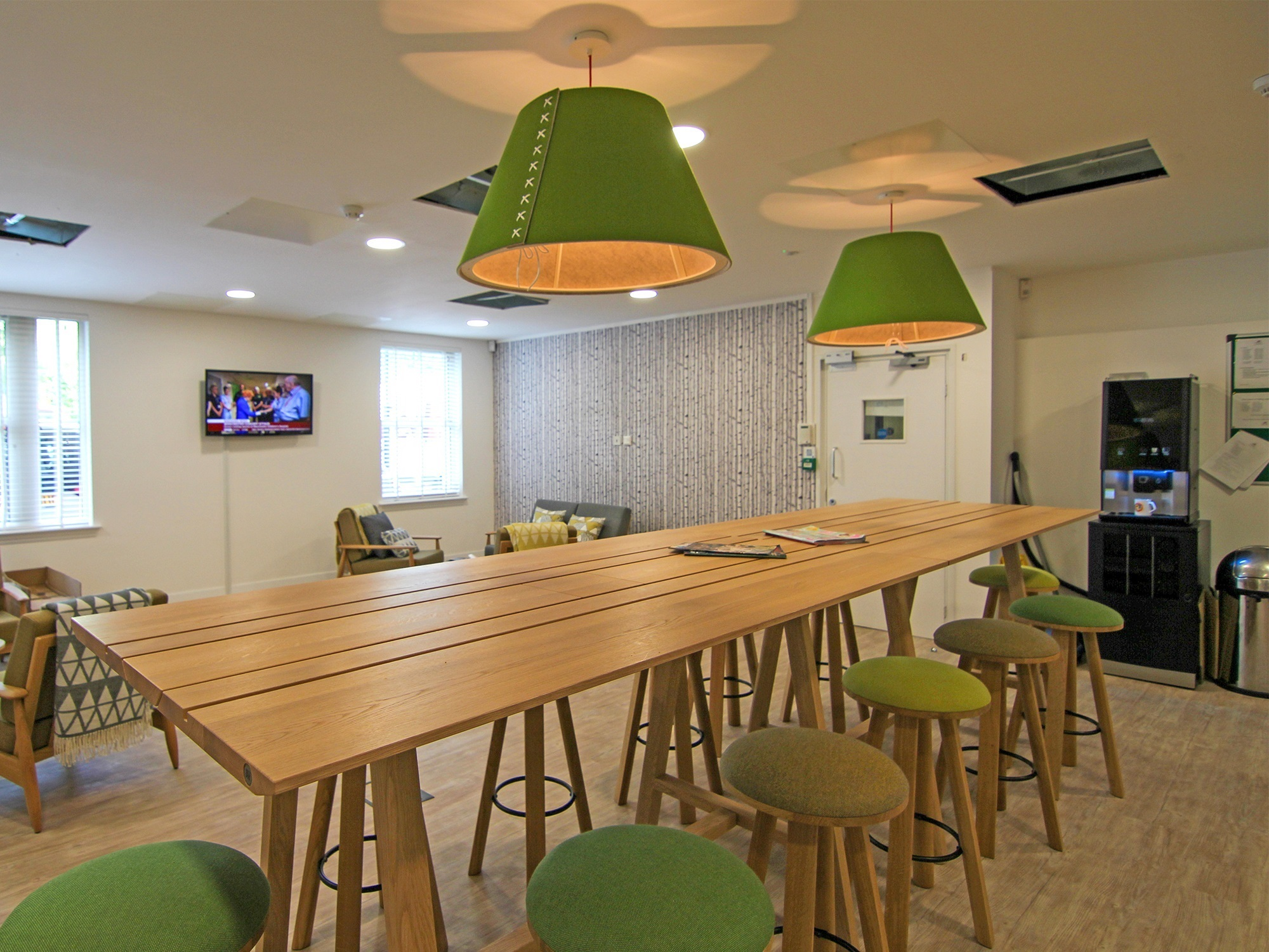 communal kitchen with green stools and lampshades
